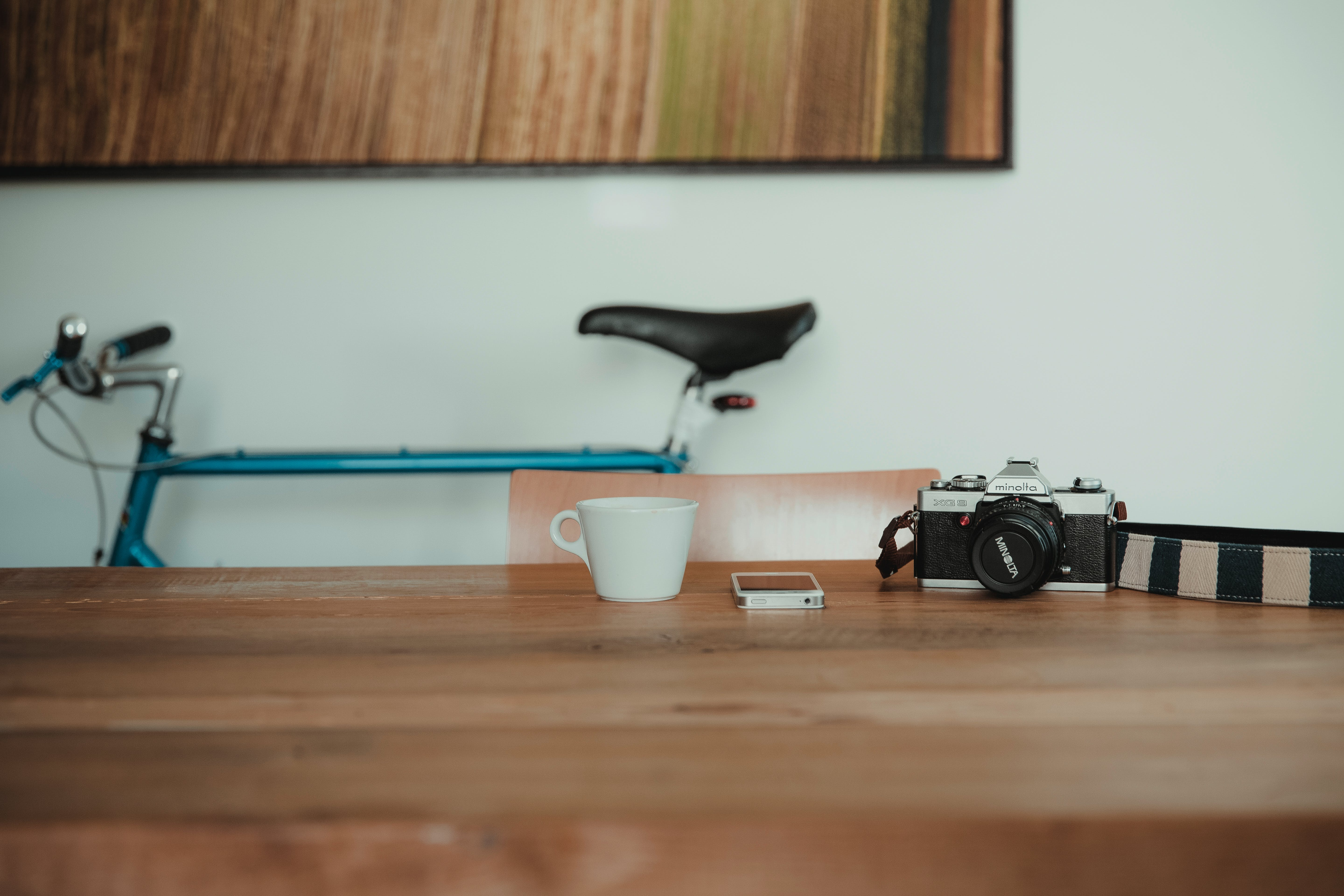 Black Camera Beside White Smartphone and Teacup on Brown Wooden Table