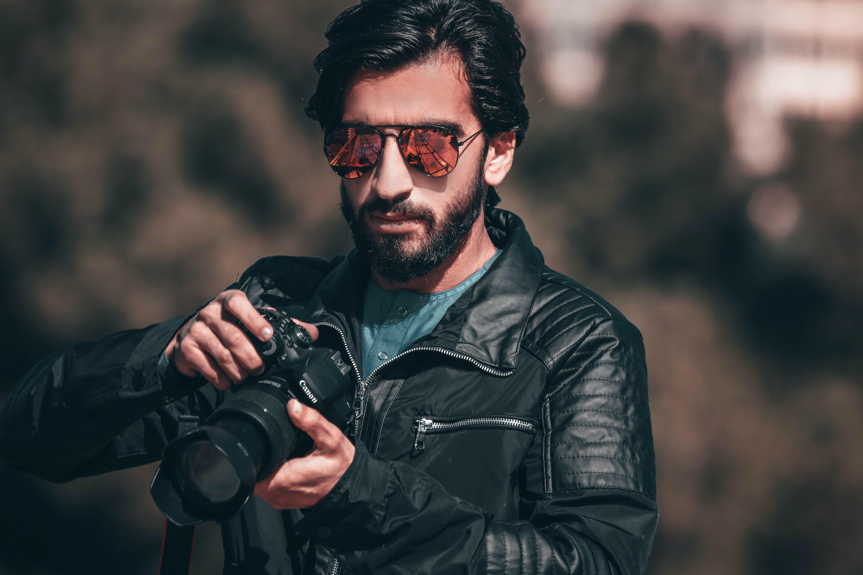 Man Holding Black Canon Dslr Camera