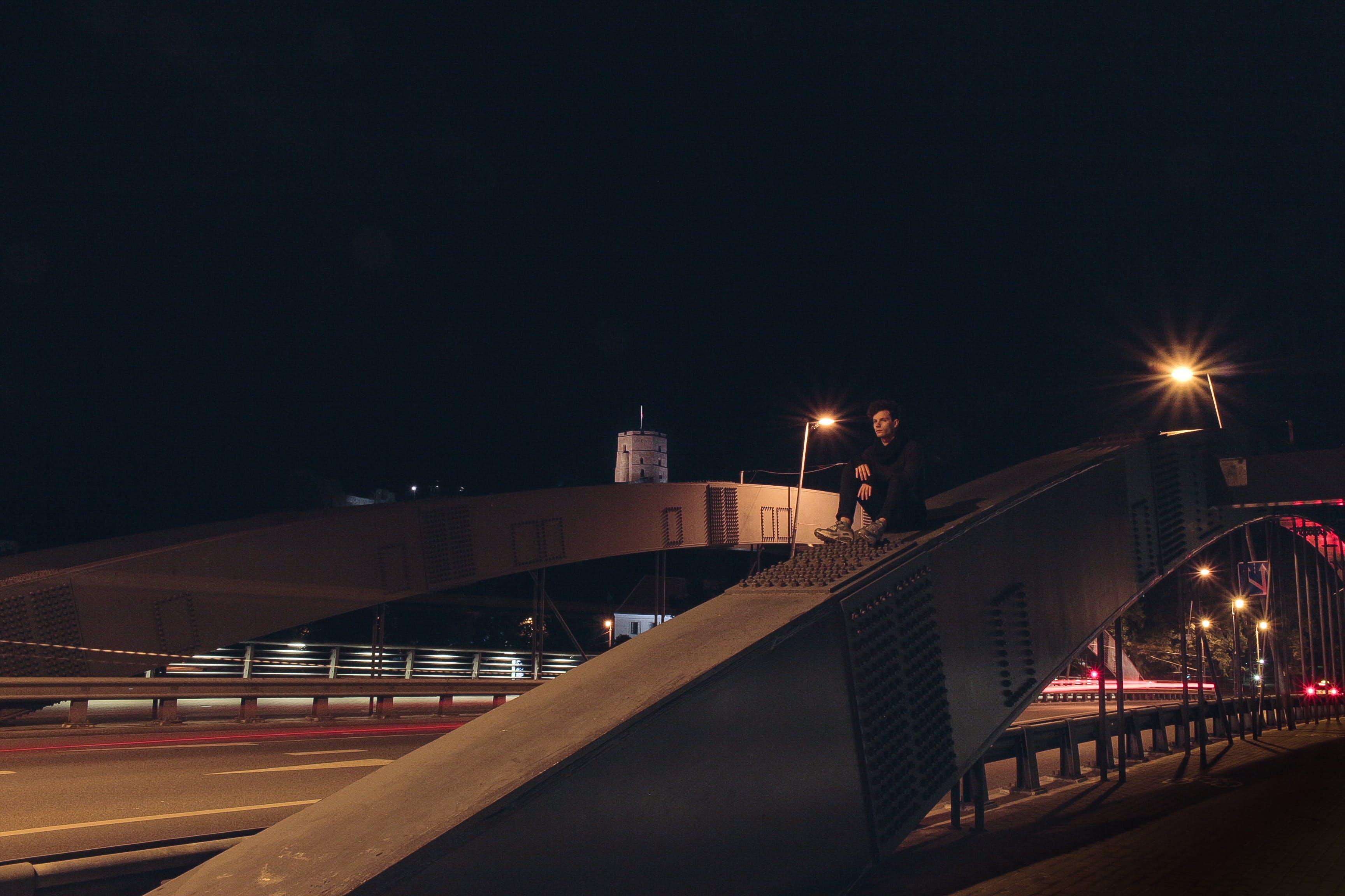 Man Sitting on Gray Steel Bridge