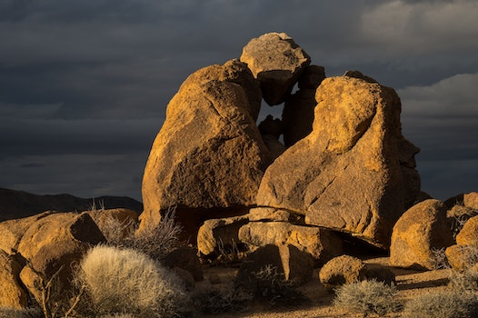 Rock Formed Person Under Heavy Clouds during Daytime
