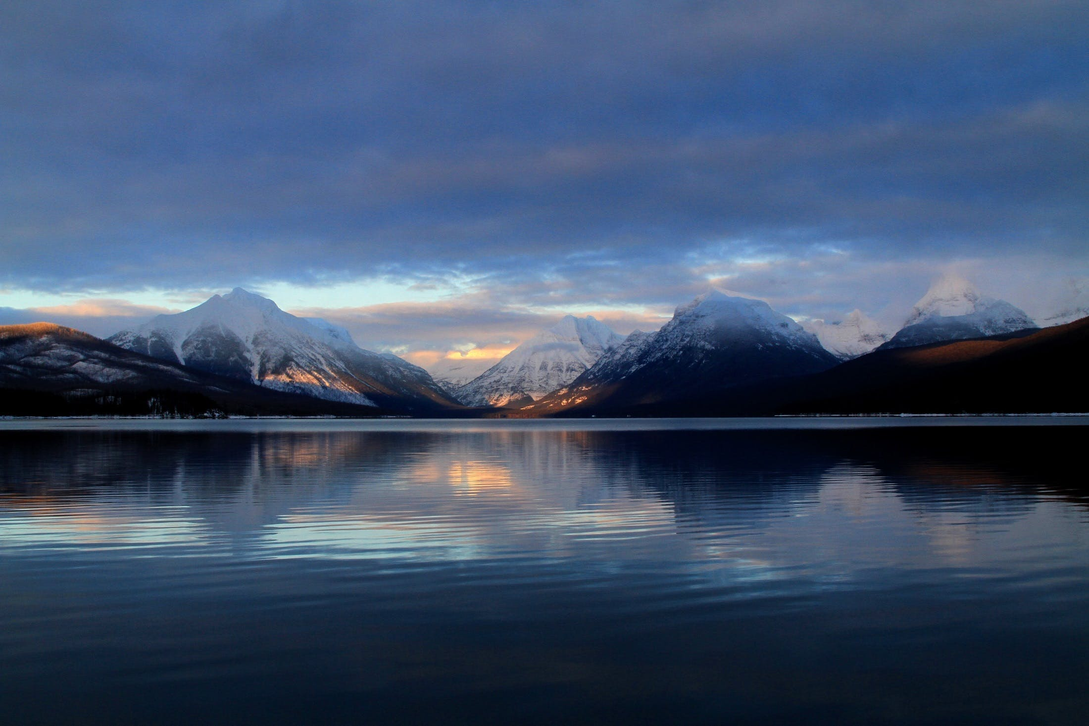 Body of Water in a Distant of Mountains Under White Clouds