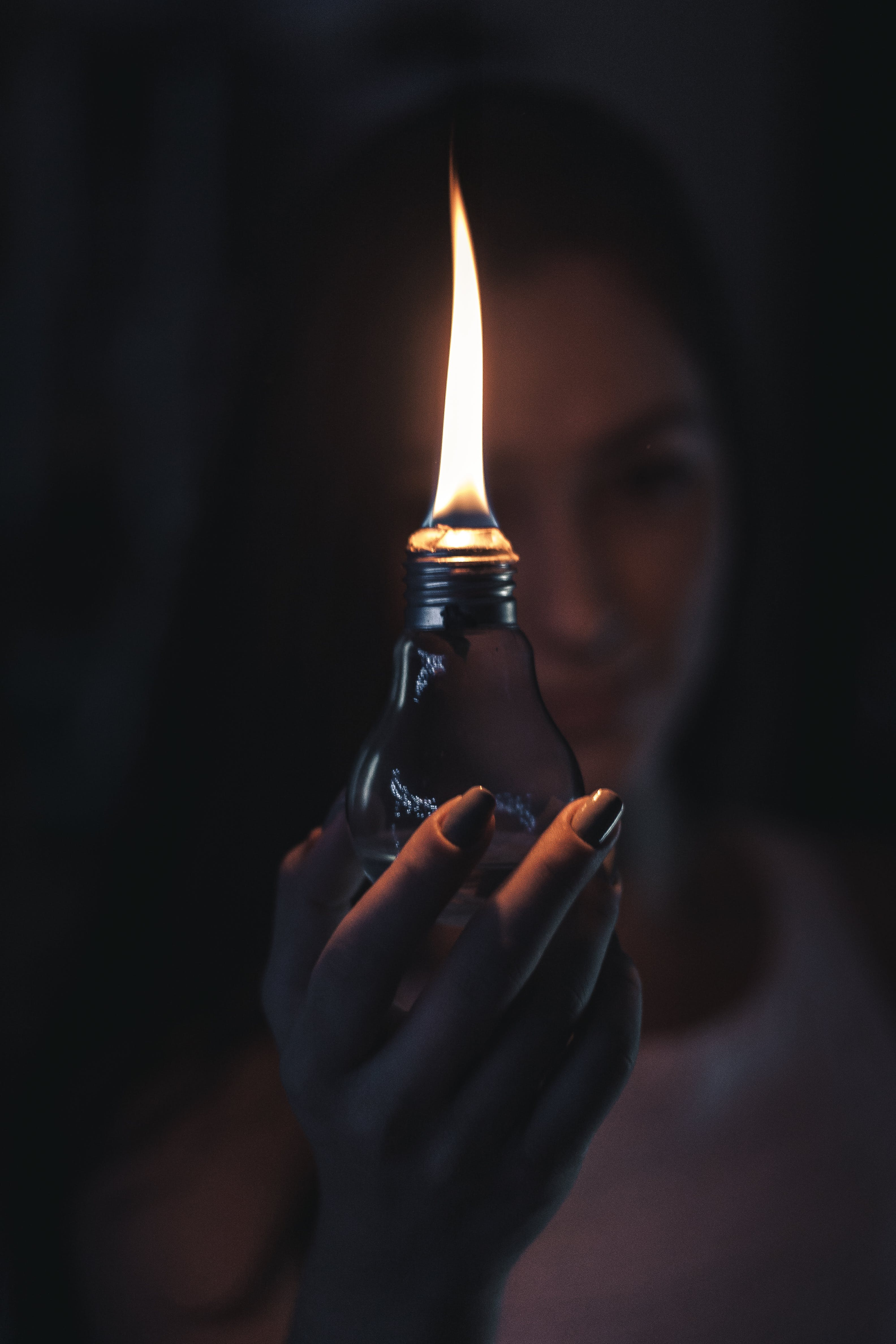 Woman Holding Lighted Oil Lamp