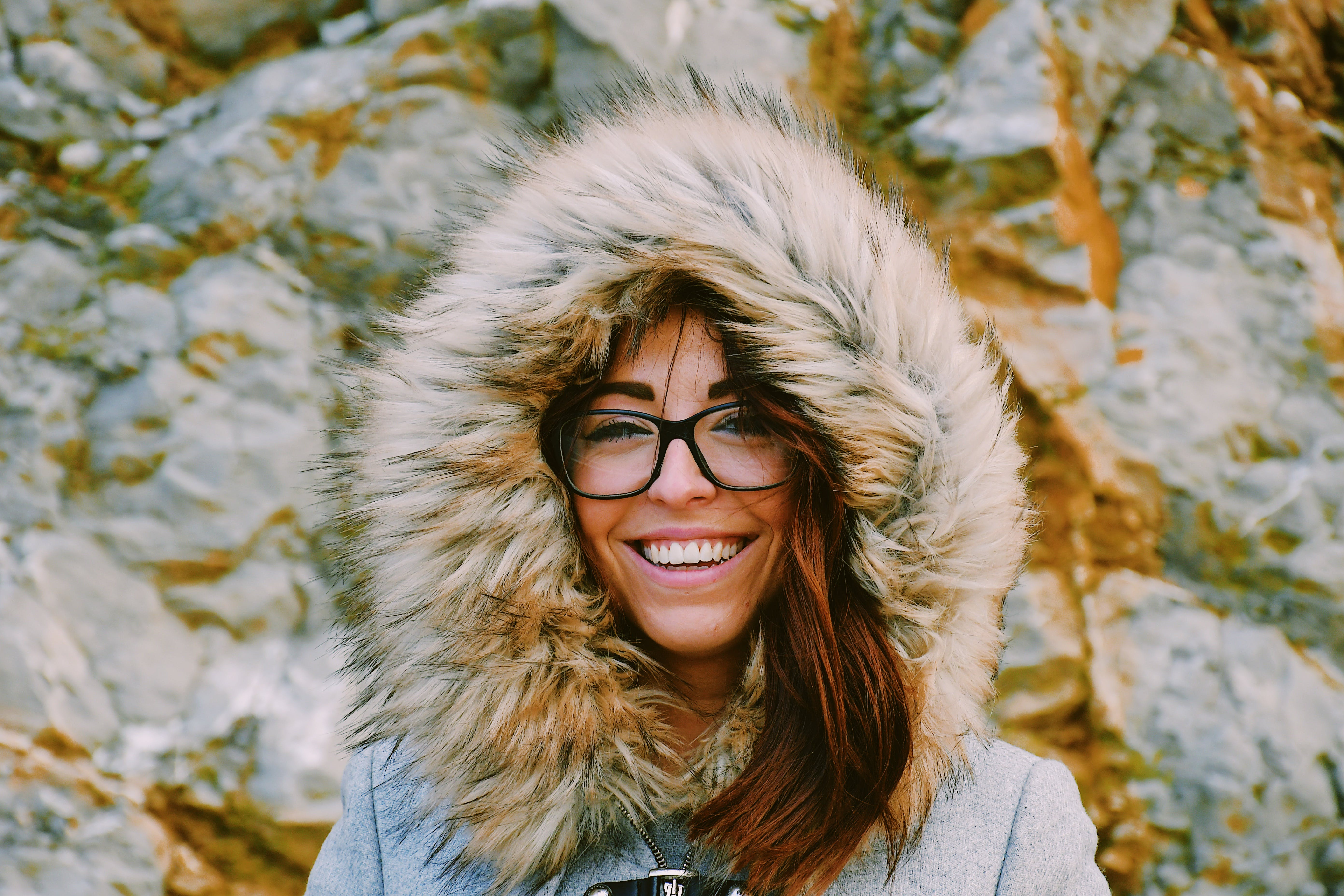 Woman Wearing Eyeglasses While Smiling Near Rock Formation