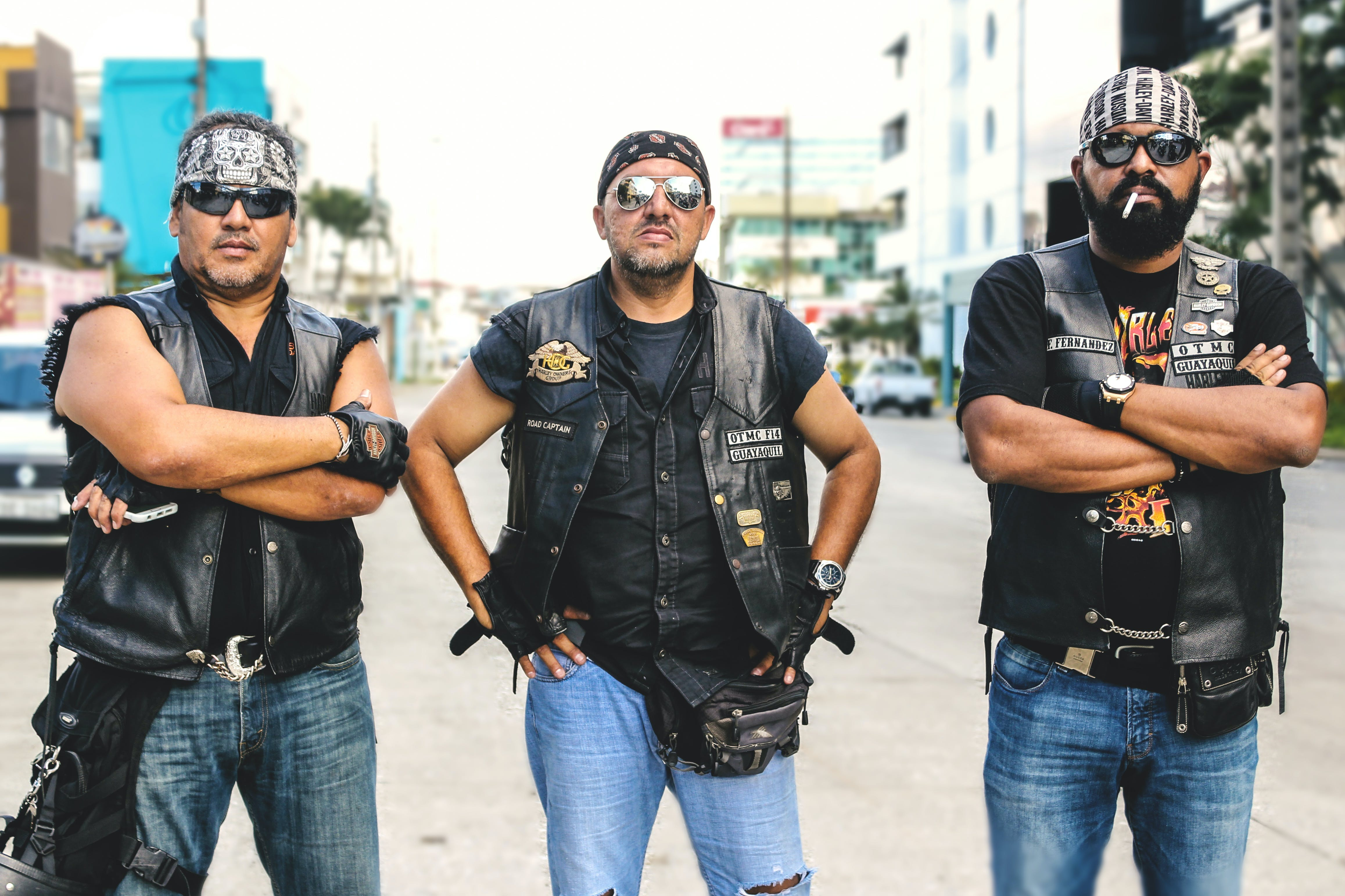 Three Person Wearing Black Leather Vest