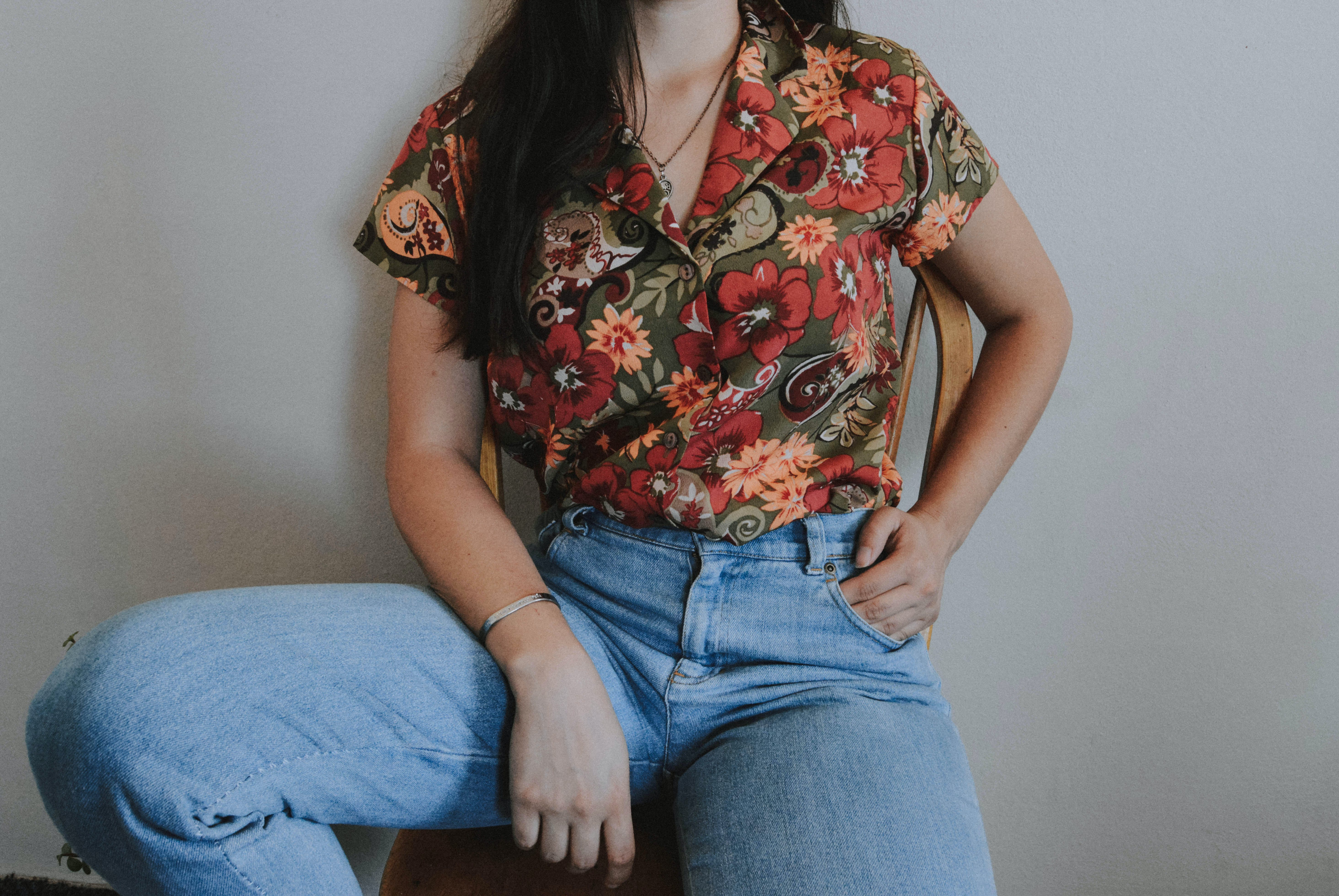 Woman Wearing Multicolored Floral Button-up Shirt and Blue Denim Jeans While Leaning on Wall