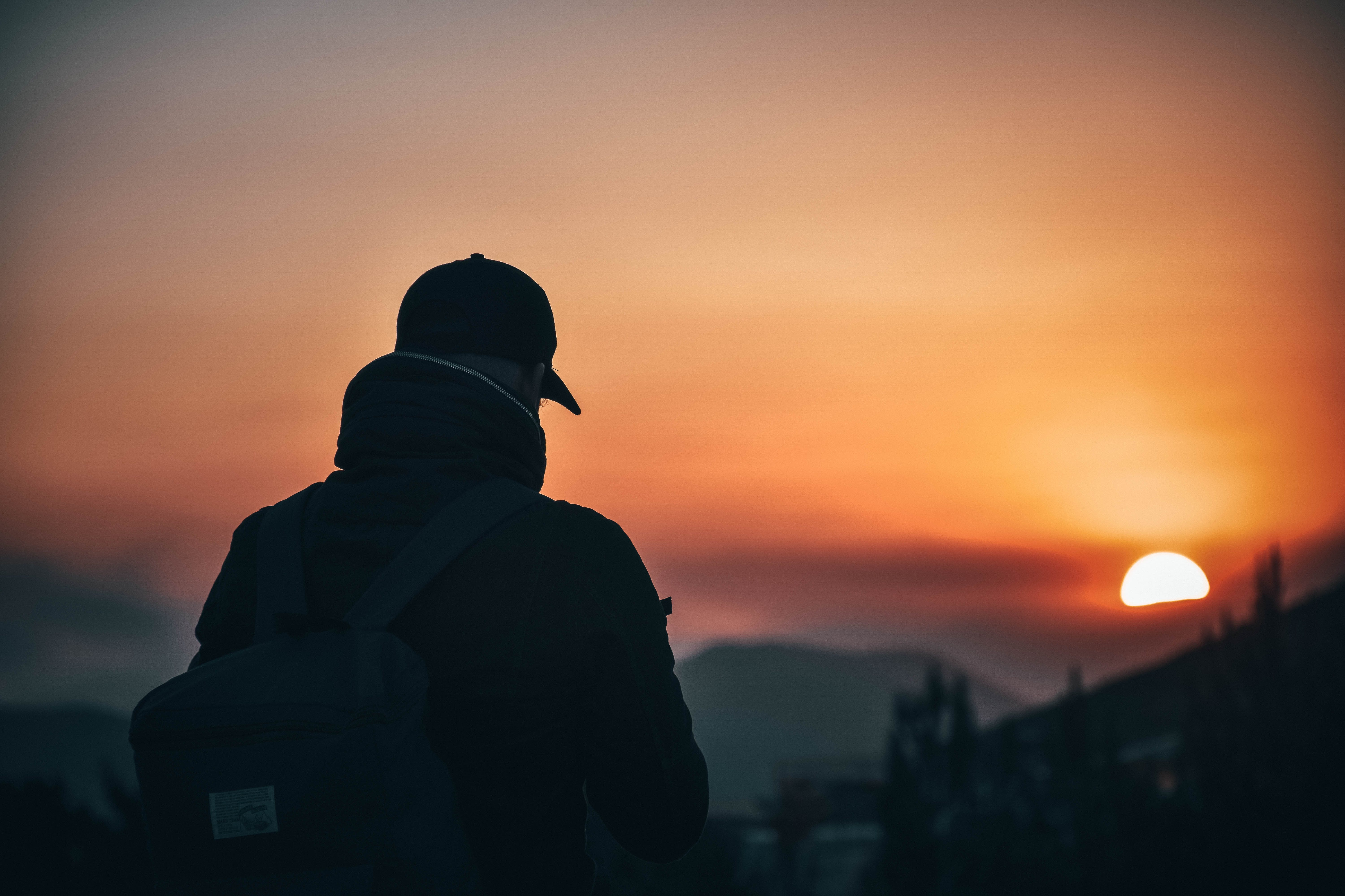 Man Wearing Baseball Cap and Backpack at Golden Hour