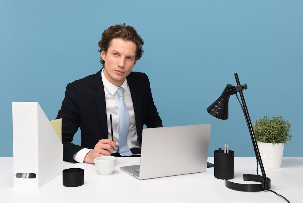 Man sitting on desk   Photo: Pexels