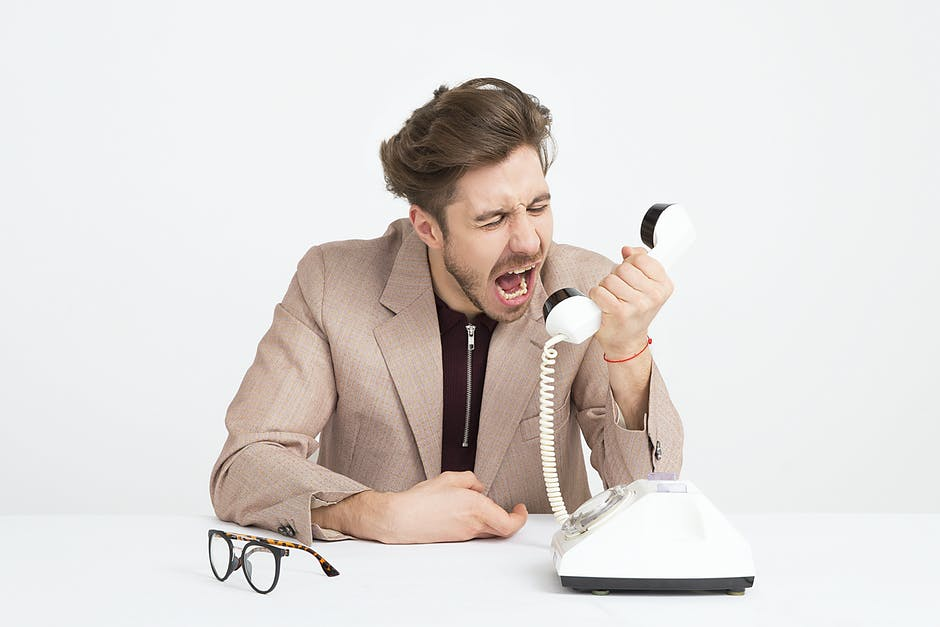 Man Wearing Brown Suit Jacket Mocking on White Telephone