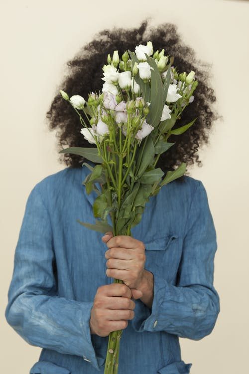 Person Holding White Flower Bouquet Covering Face