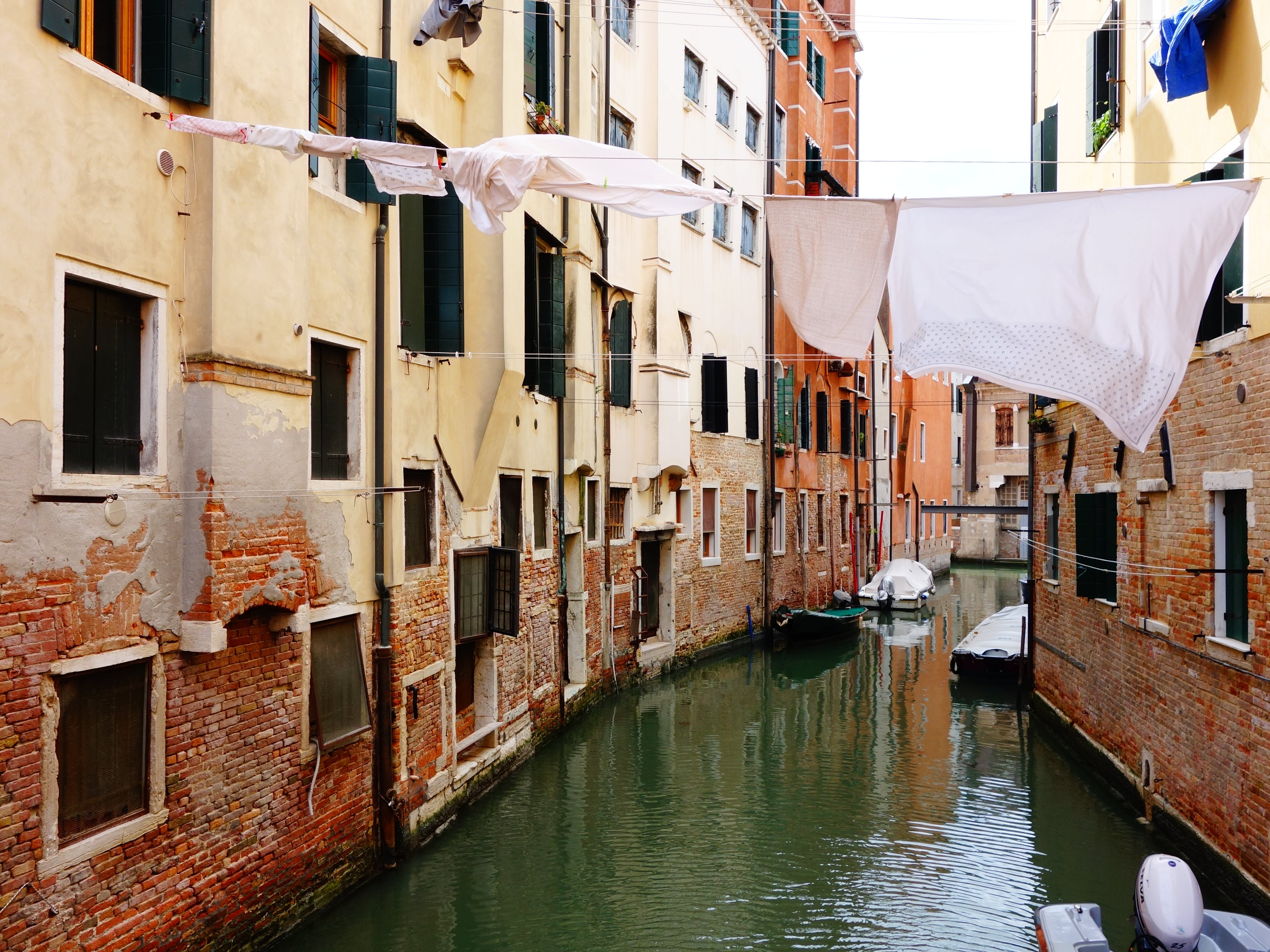 Free stock photo of apartment buildings, building exterior, canal, clothes