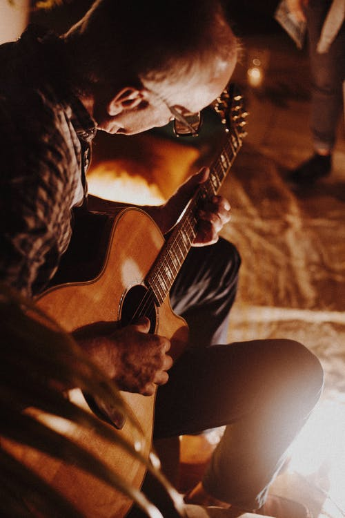 Photo of Man Playing Guitar
