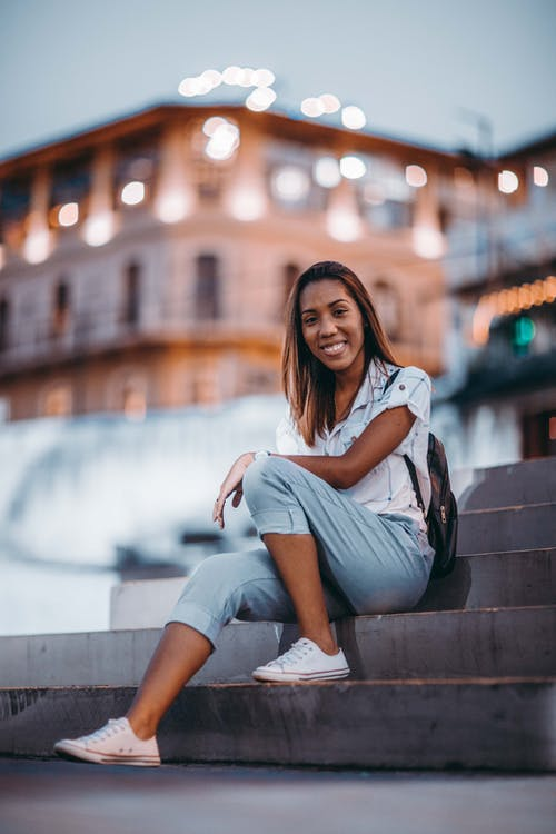 Smiling Woman Sitting in Stairs on Shallow Focus Lens