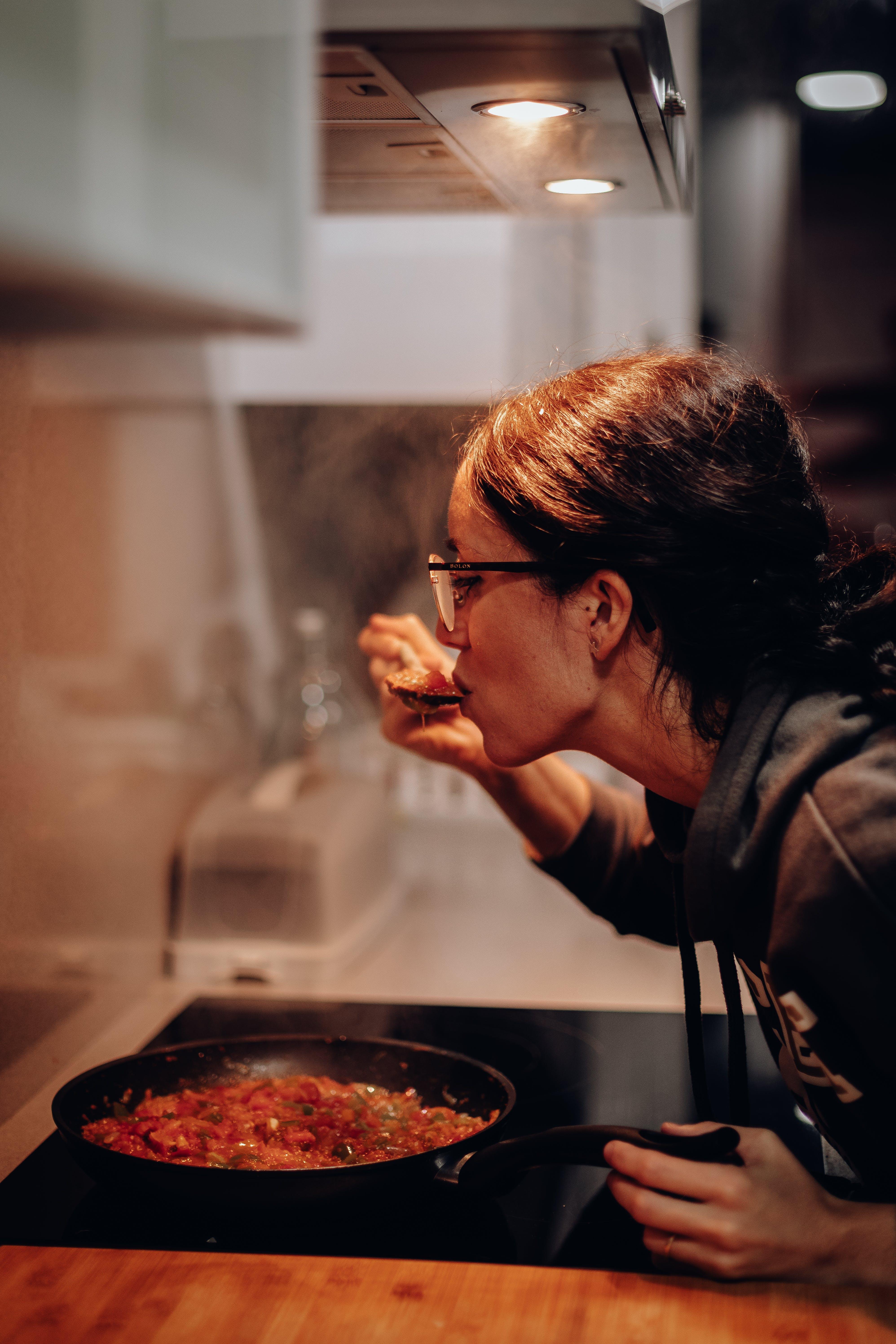 Woman Eating on Cooking Pan
