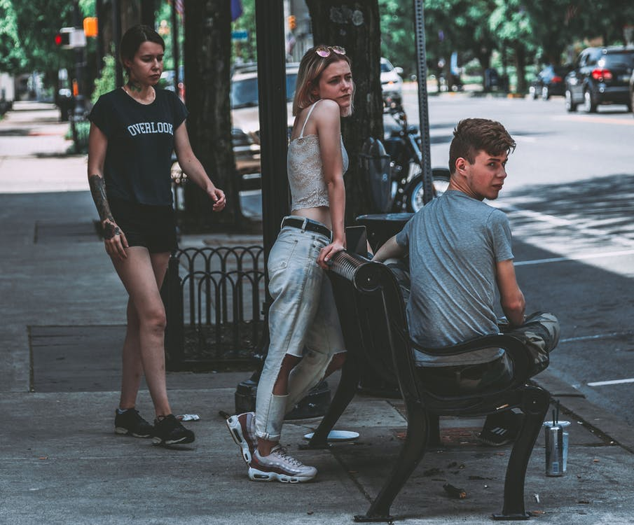 Three Person Staying on Sidewalk