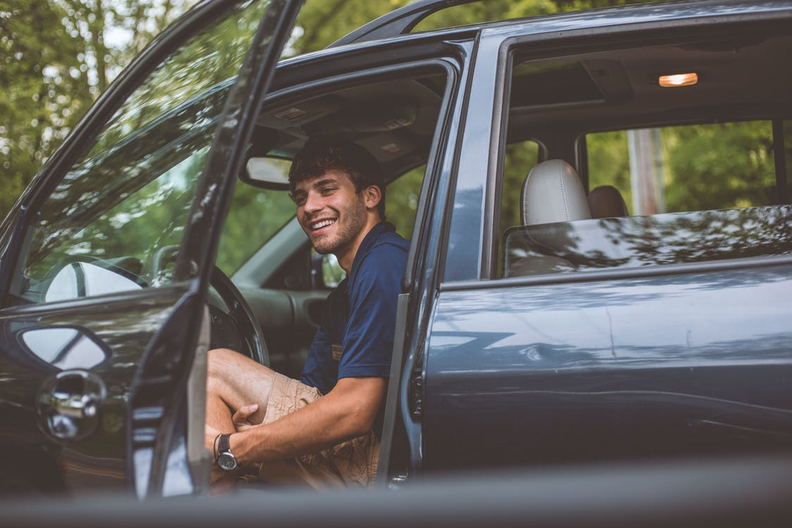 Man Inside Vehicle in Front of Opened Door