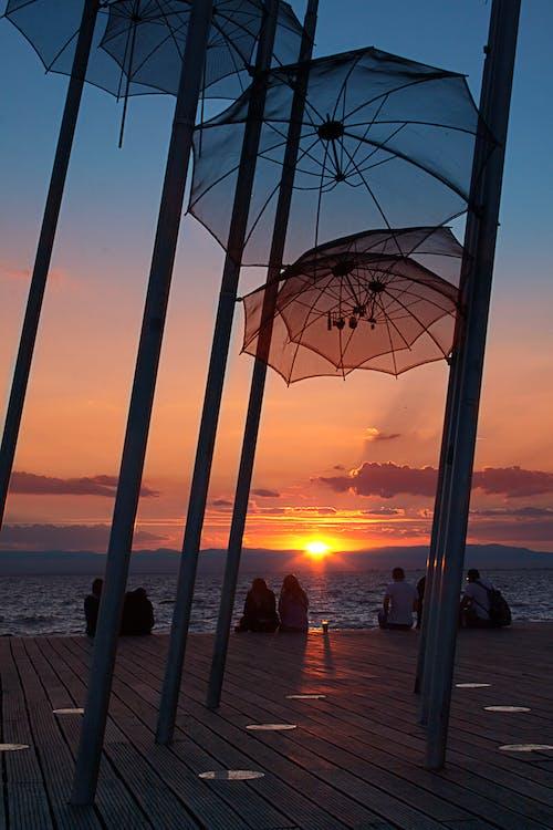 Umbrellas Hanged on Poles Near Dock