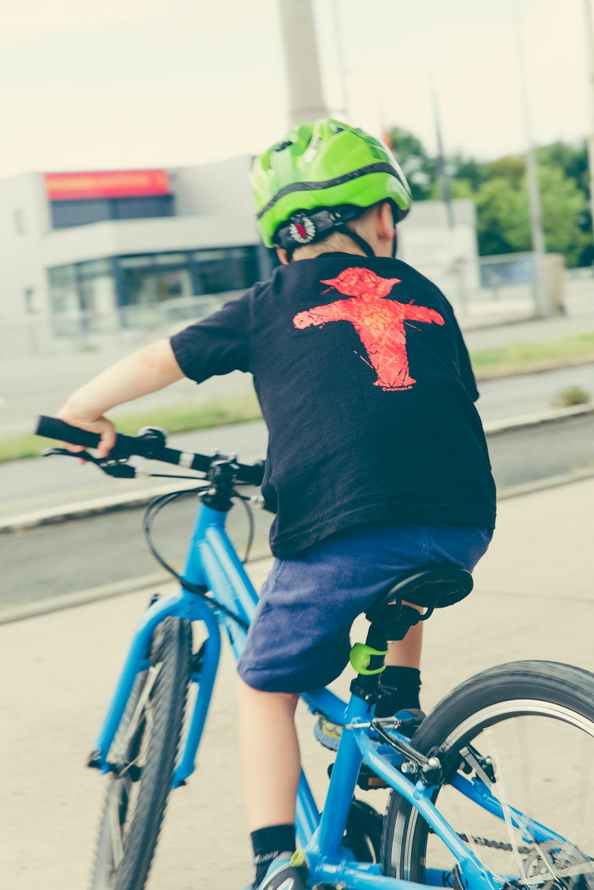 a kid riding a bike with his helmet on