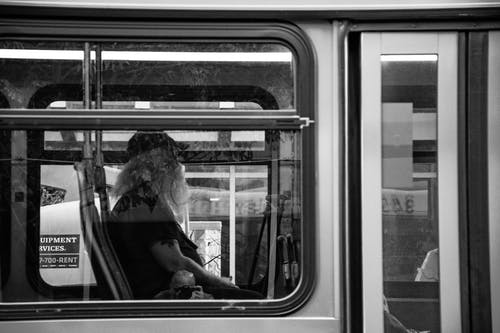 Grayscale Photography of Man Sitting Inside Bus
