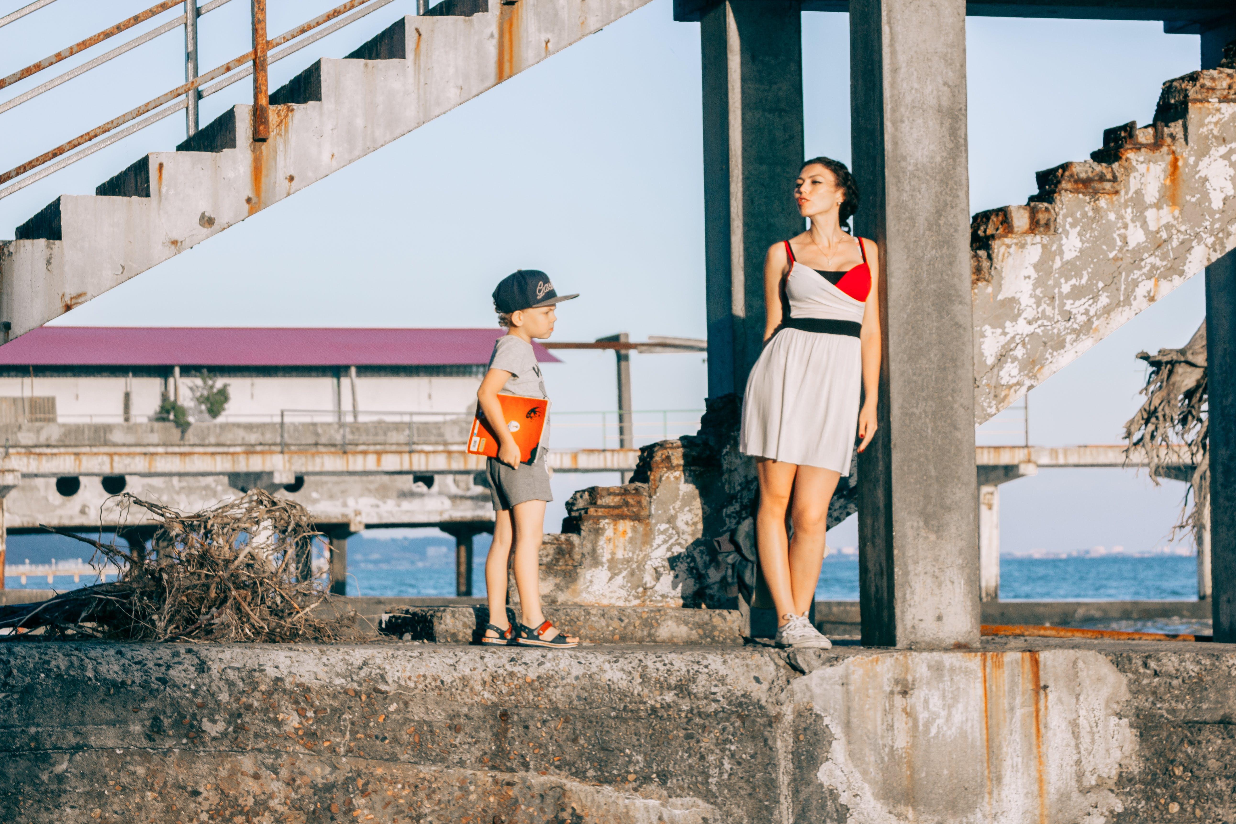 Woman Beside Girl Under Concrete Bridge
