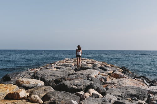 Woman in Black Shirt and Blue Denim Shorts Standing on Rocky Shore