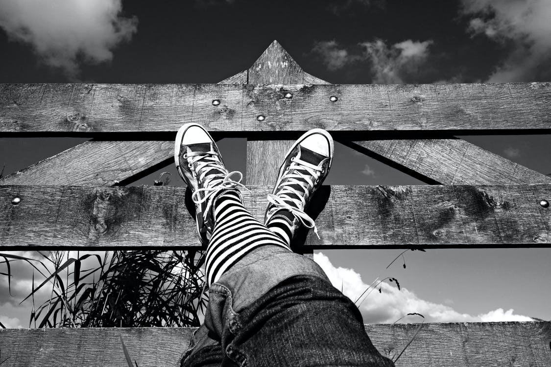 Grayscale Photo of Person's Shoes