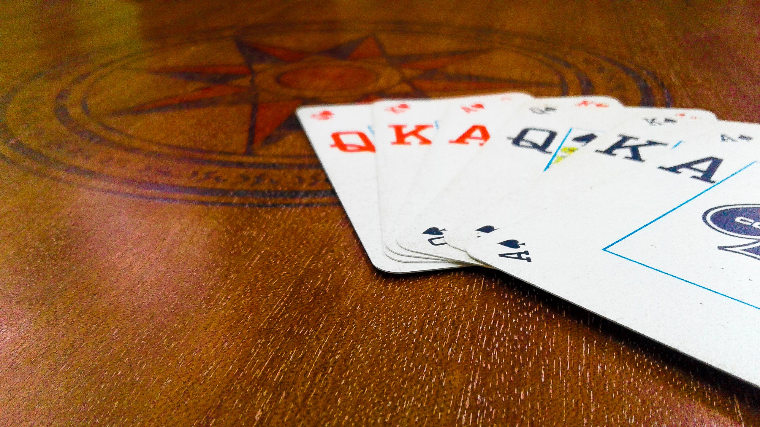 Assorted Playing Cards on Brown Wooden Surface