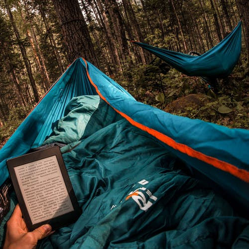 Person Holding Amazon Kindle While Lying on Hammock Beside Other Camper
