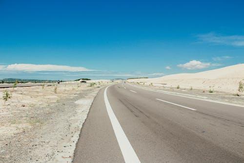 Gray Asphalt Road Under White and Blue Skies