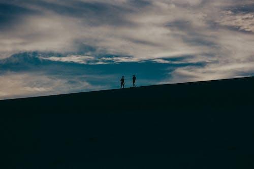 Foto profissional grátis de andando, areia, casal, céu