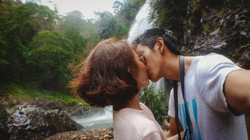 Man Kissing Woman Behind Waterfalls