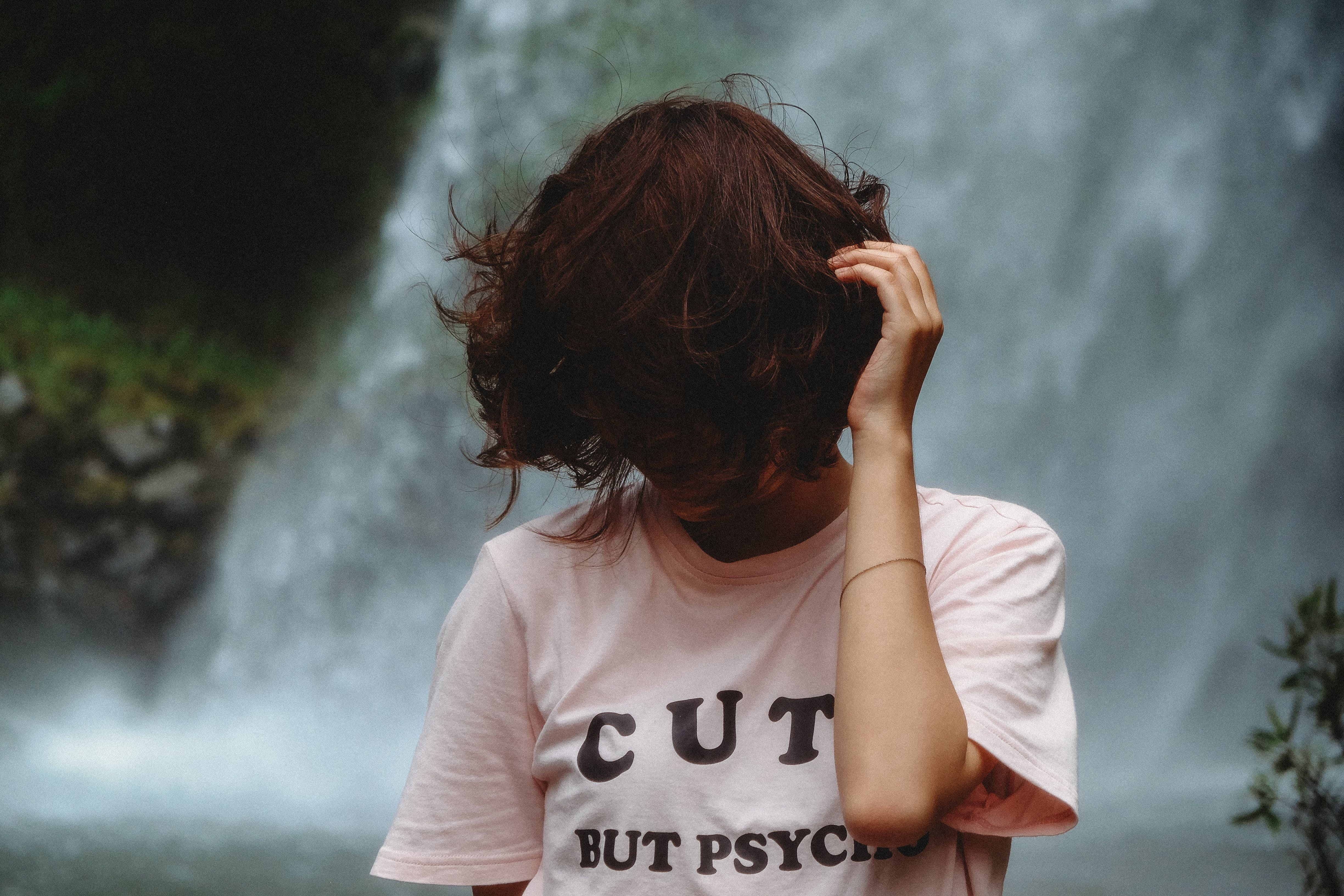 Woman Standing Looking Down While Holding Hair Near Waterfall