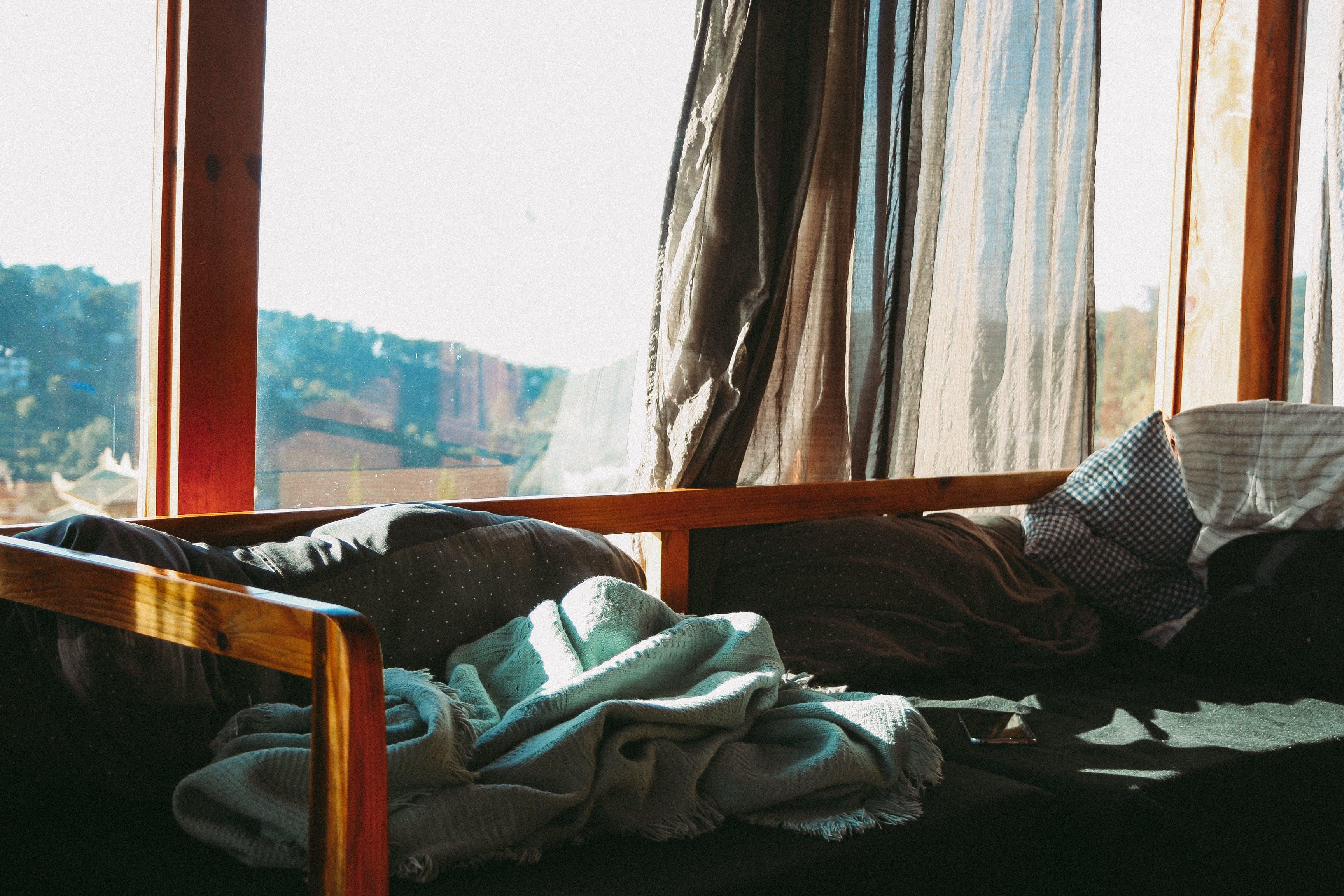 Brown Bed Beside Glass Window