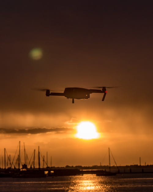 White Quad-copter Drone Flying over Body of Water during Golden Hour