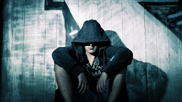 person wearing black zip hoodie sitting in front of gray wooden plank wall during nighttime