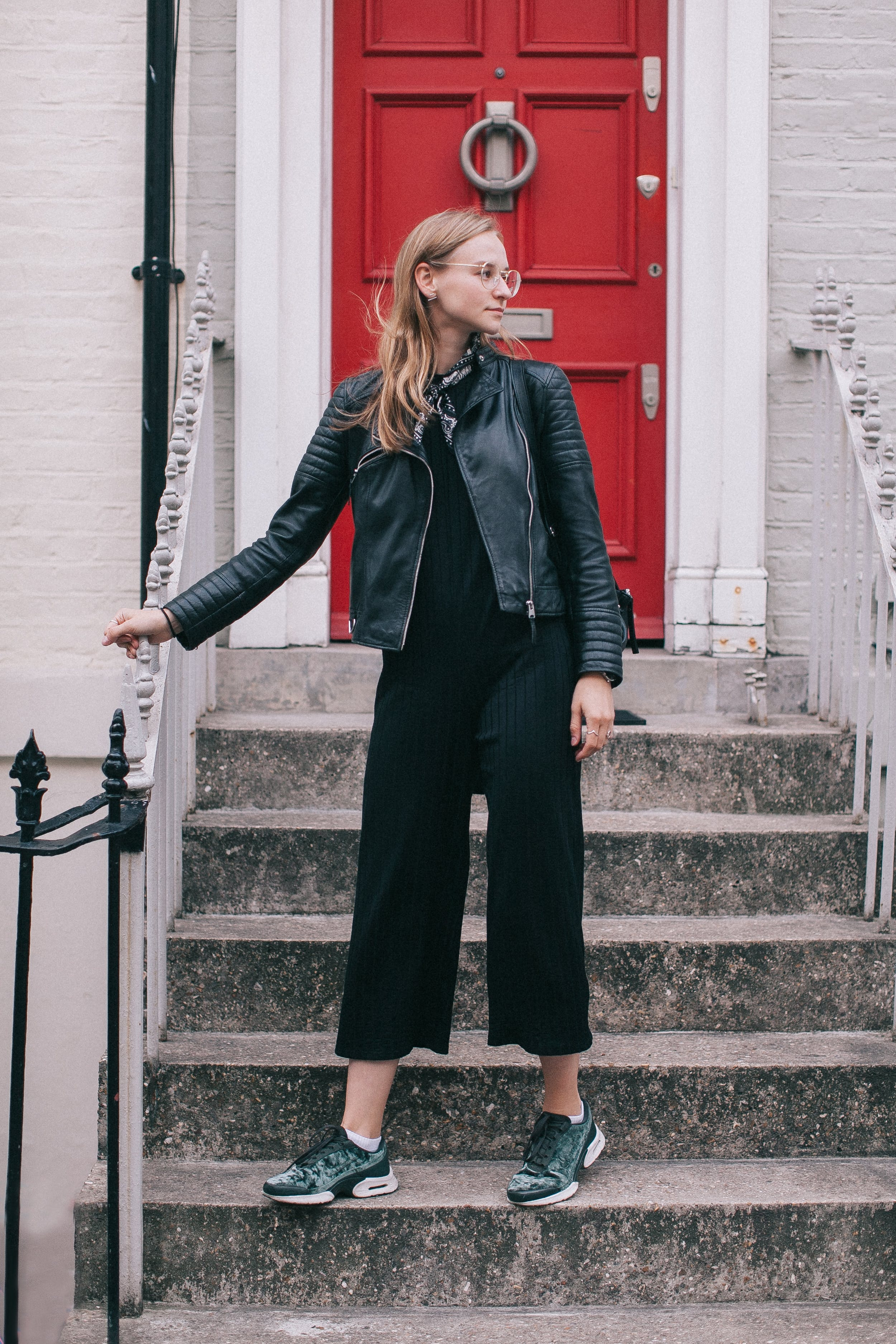 Woman Wearing Black Leather Jacket Standing on Stairs