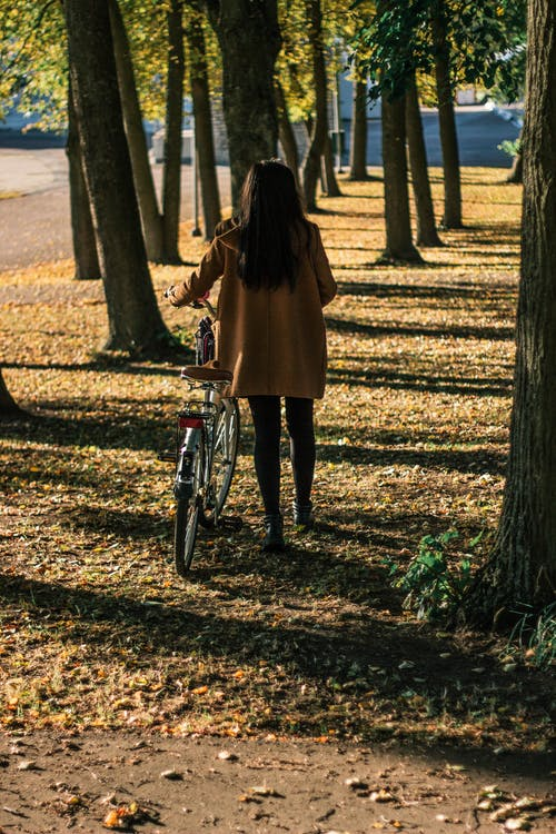 Woman Holding Bicycle Near Trees