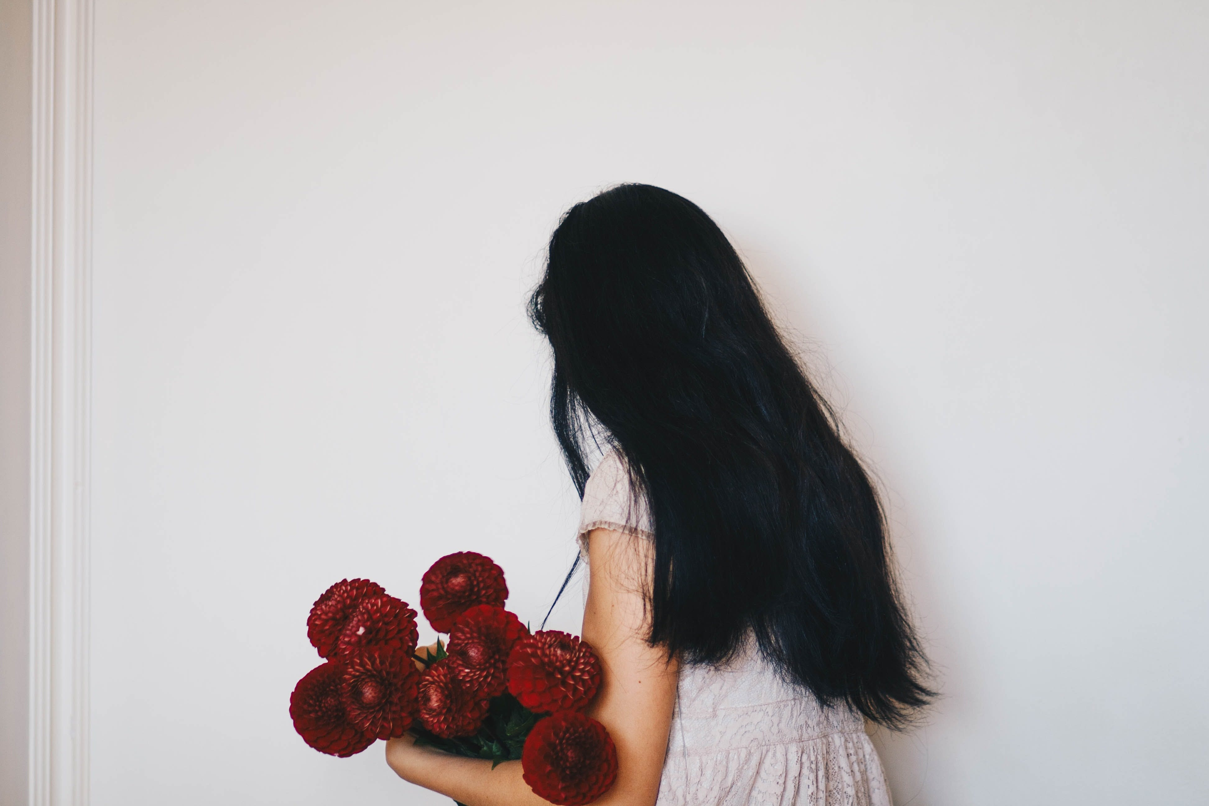 Woman Holding Bouquet of Red Dahlia Flowers