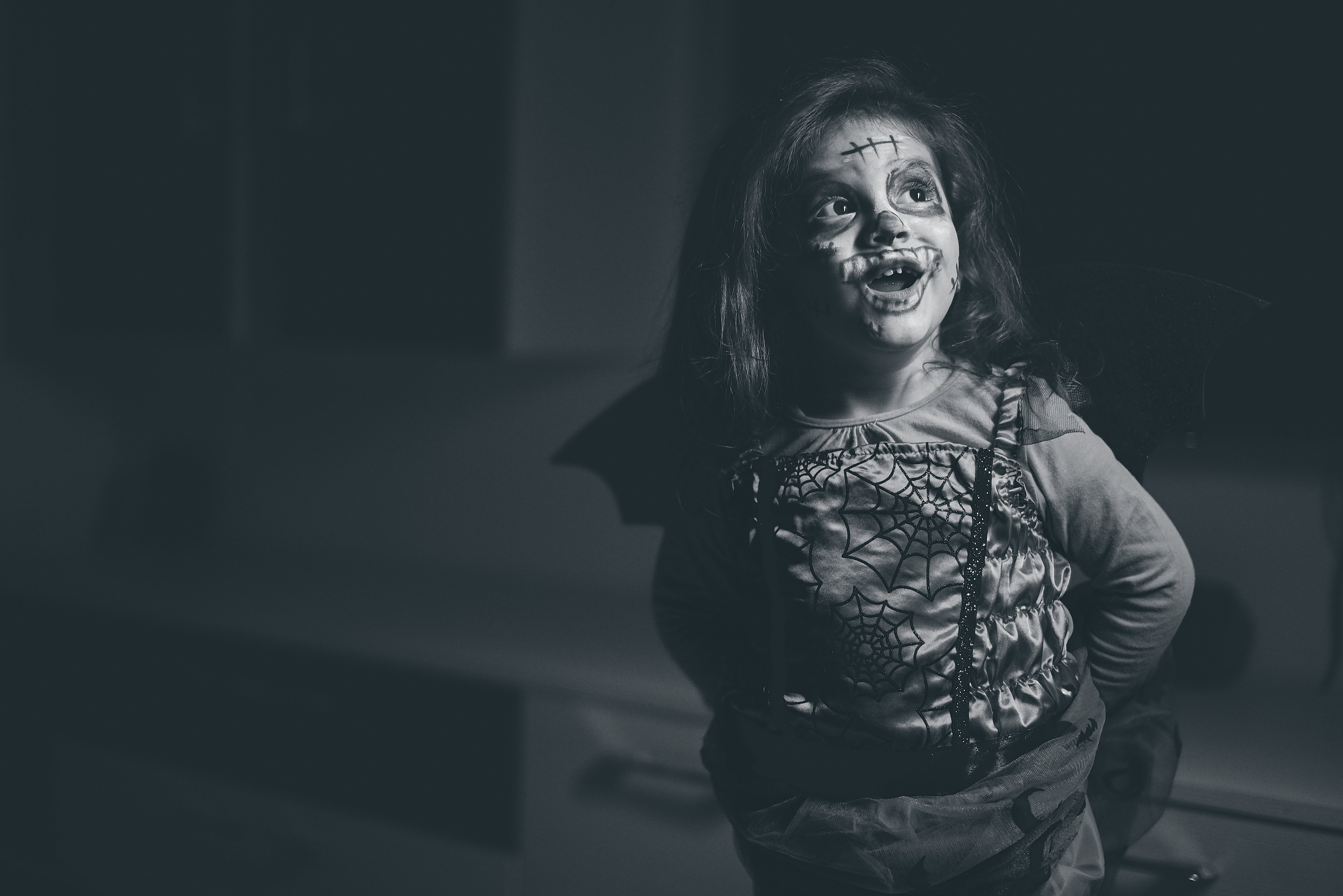 Grayscale Photo of Smiling Girl In Halloween Costume