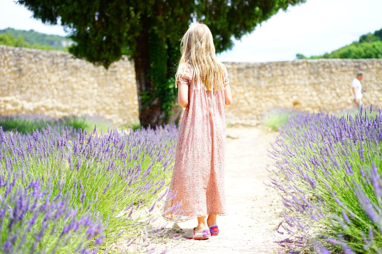 Woman Wearing Pink Maxi Dress Walking Along Unpaved Pathway With Purple Plants Nearby