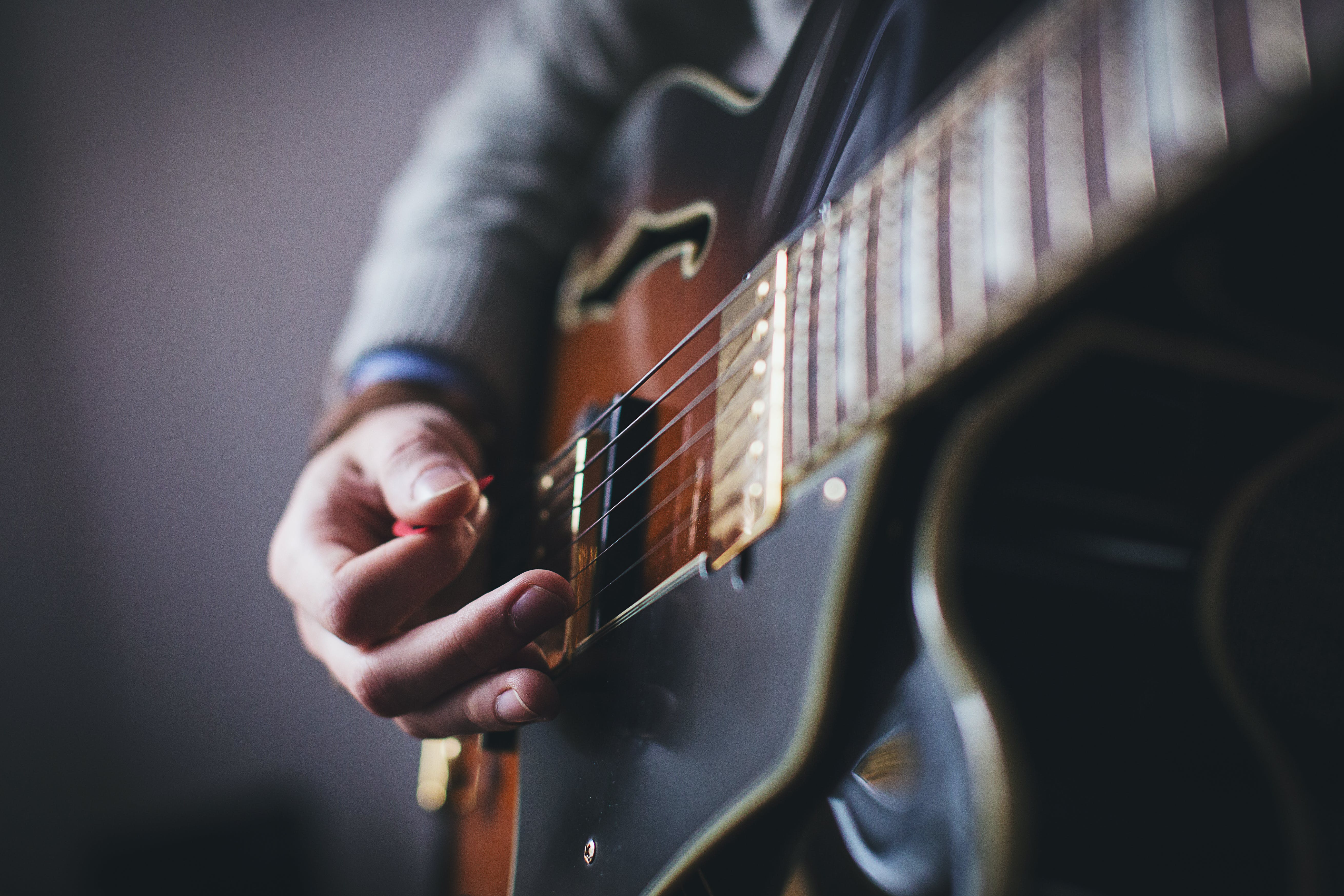 Person Playing Brown and Black Guitar