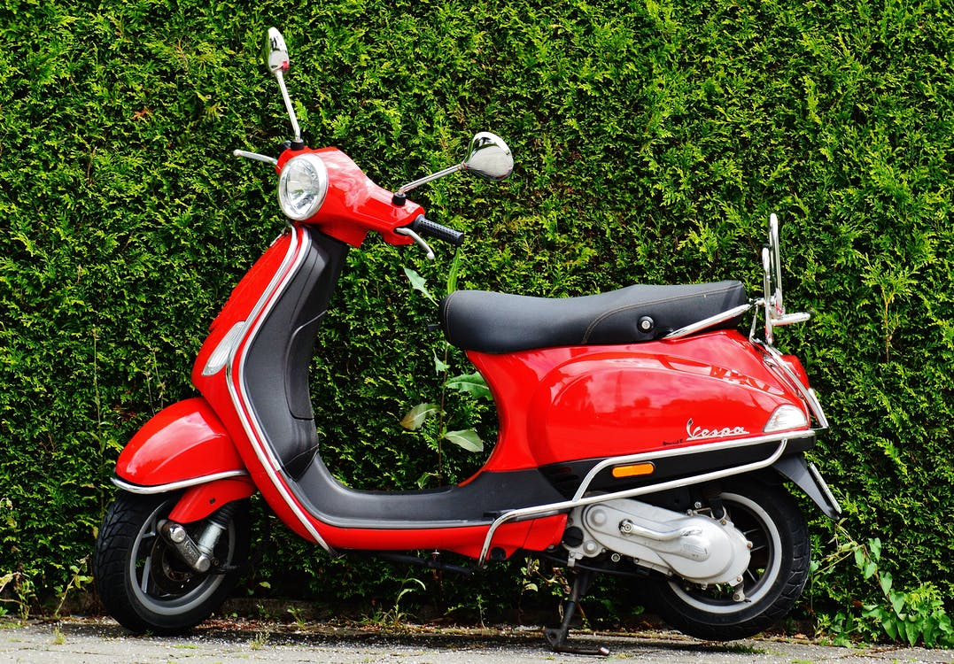 Red and Black Moped Scooter Beside Green Grass