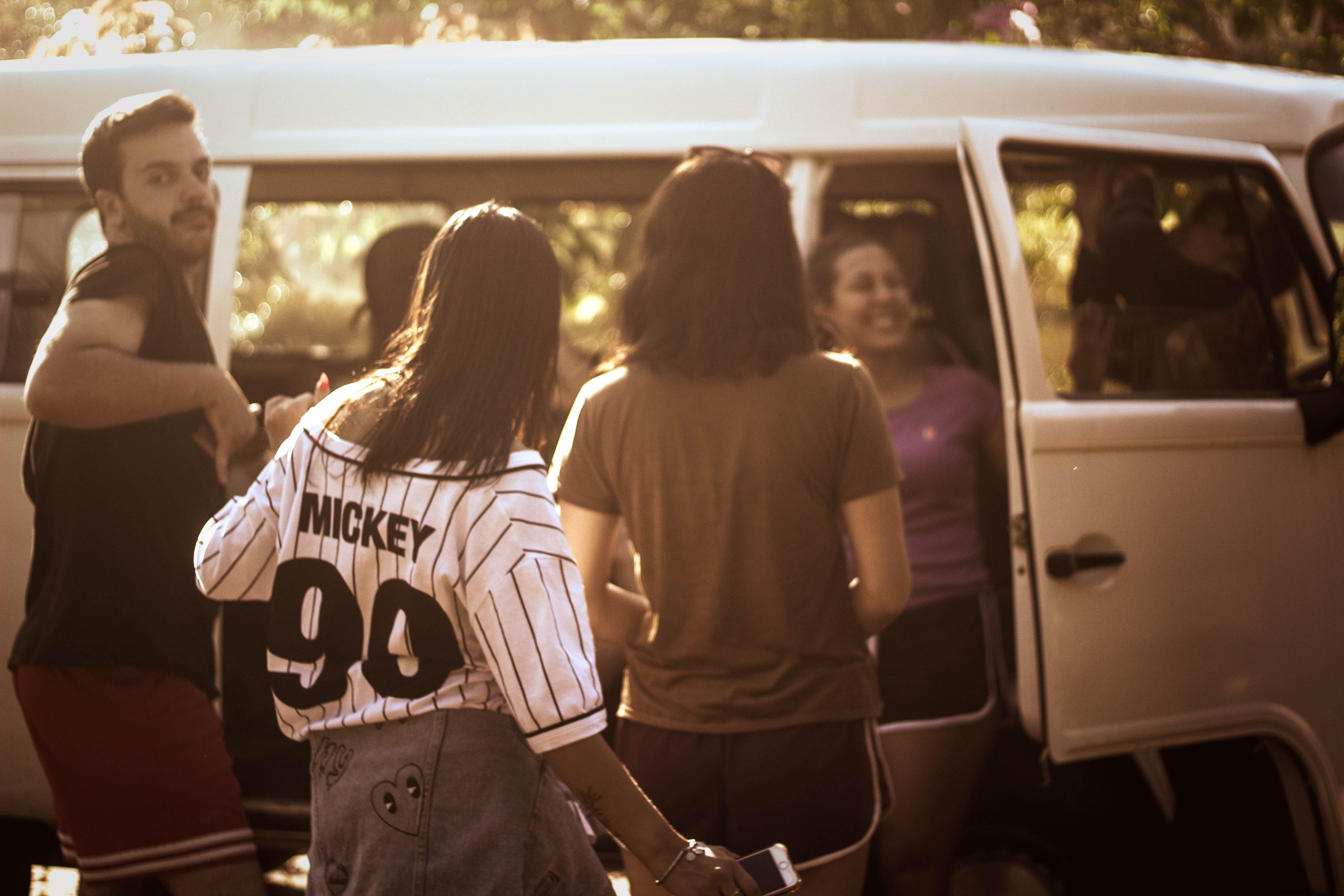 Four Person Standing Beside Van