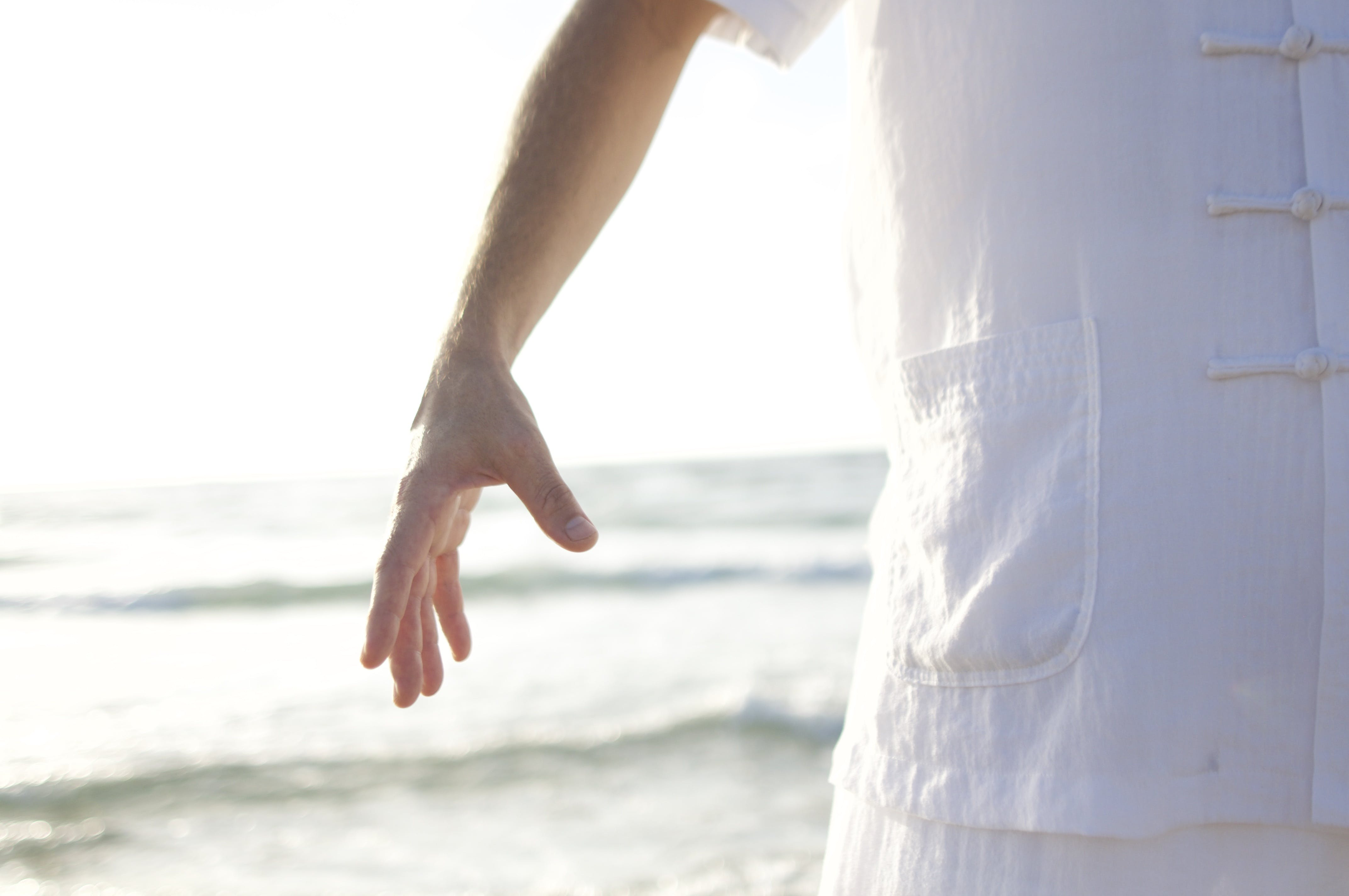 Person in White Shirt Standing on Seashore during Daytime