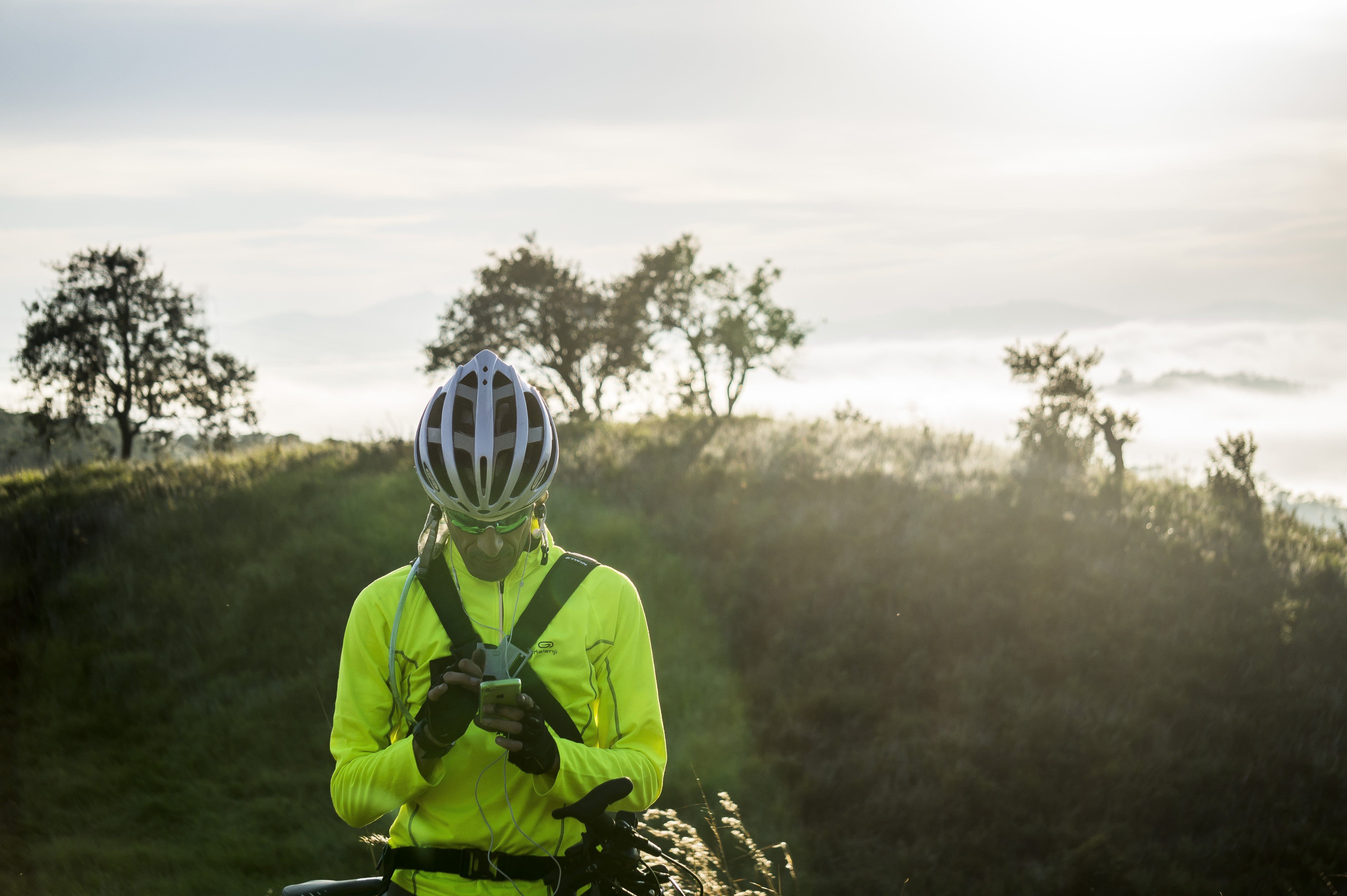 Man in Green Bicycle Suit Standing While Using His Smartphone
