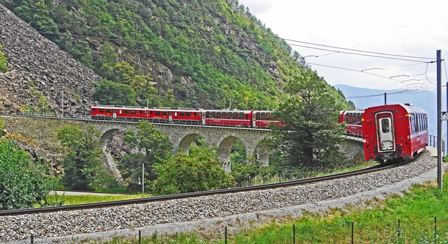 Red Train on Black Steel Train Rail during Day