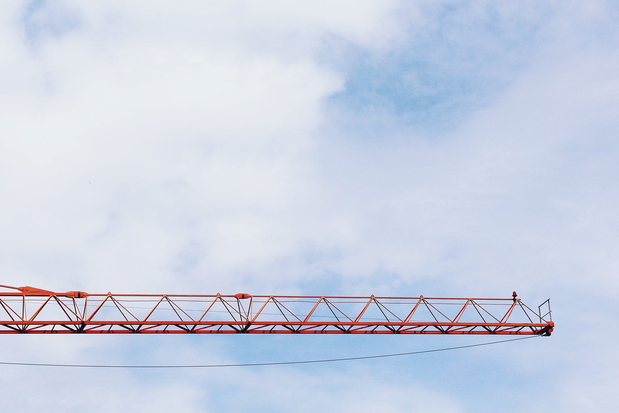 Red Crane Photo Under Cloudy Sky during Daytime