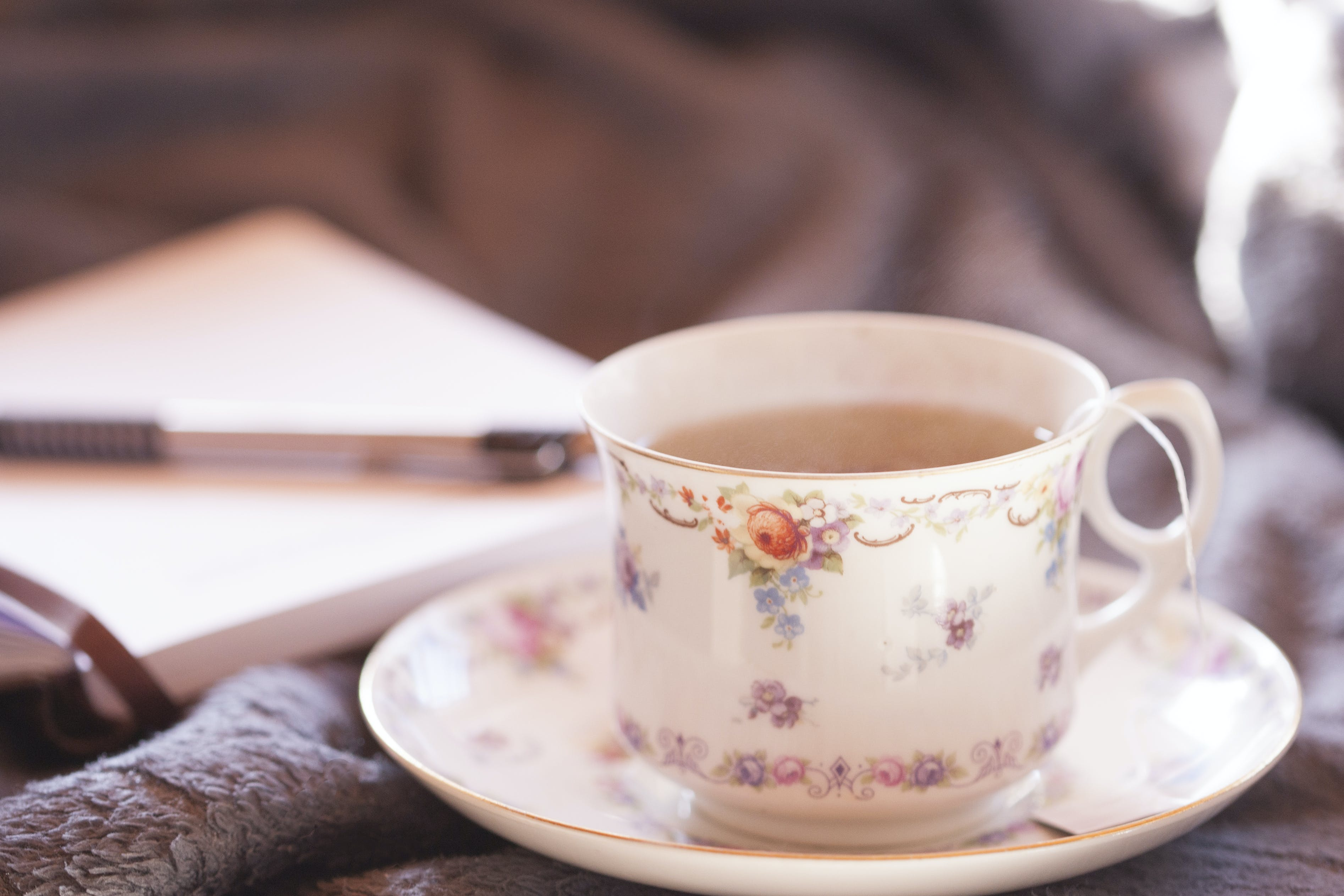 Selective-focus Photography of White and Multicolored Floral Ceramic Teacup on Saucer Filled With Coffee