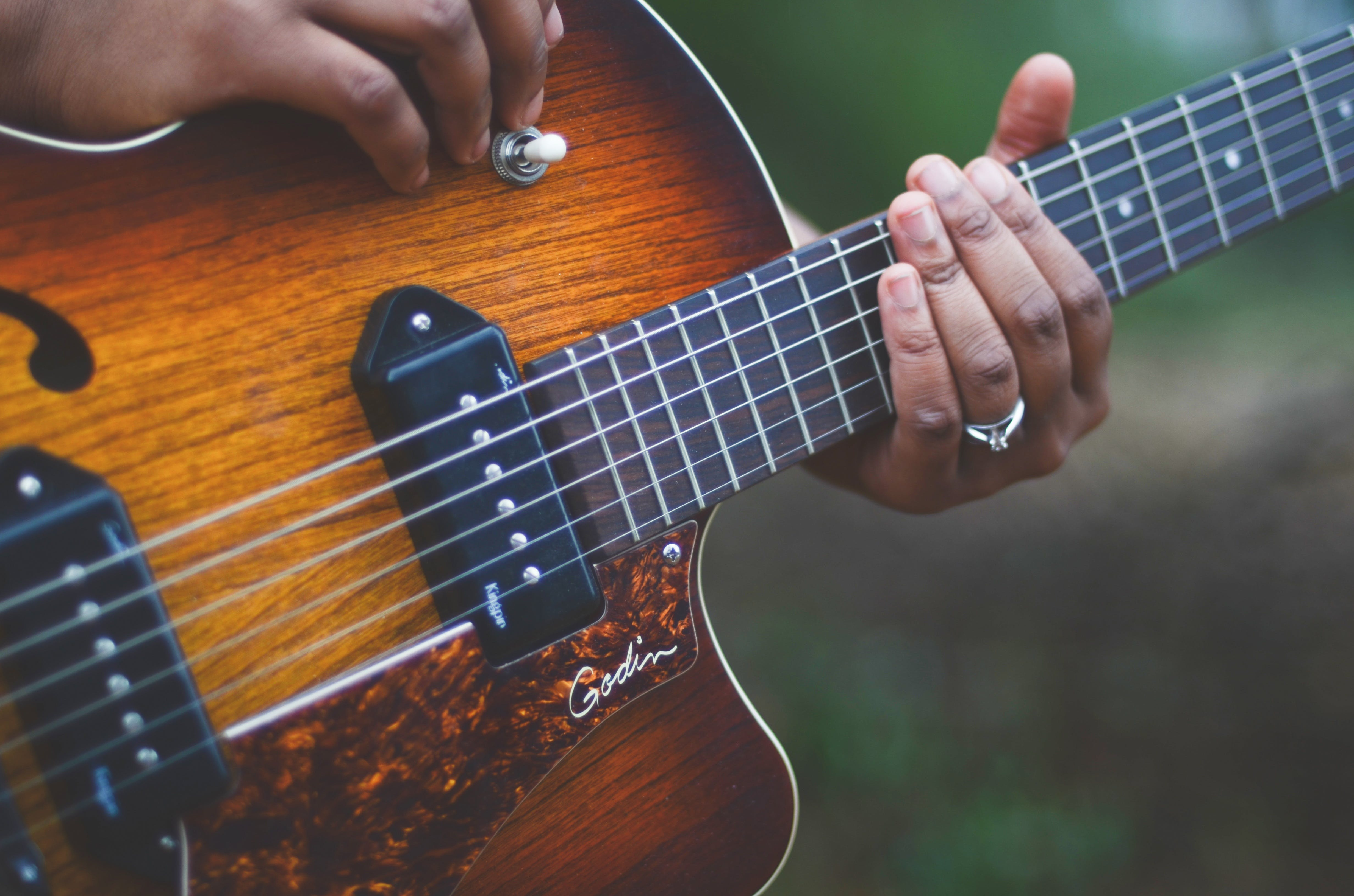 Person Holding Brown and Black Electric Guitar