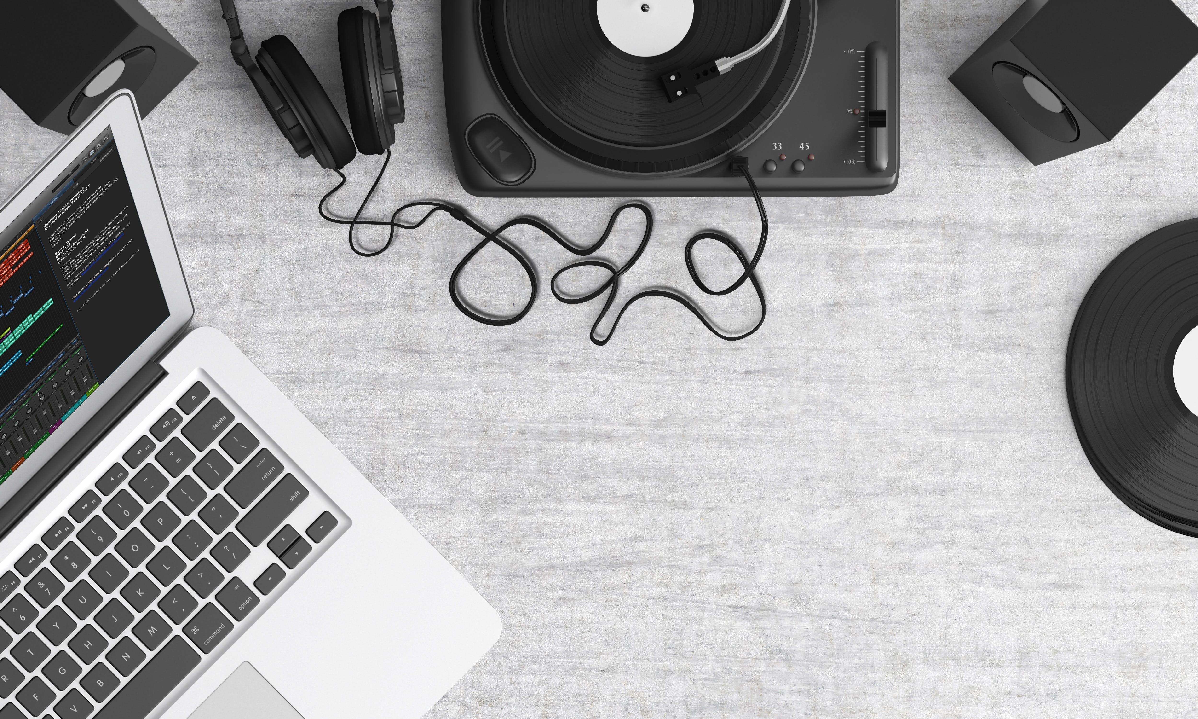 Macbook Pro Beside Black Headphones on Gray Table