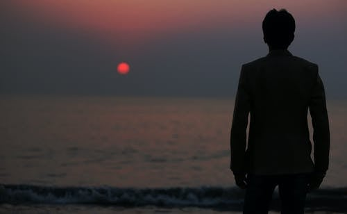 Silhouette Photo of a Man Standing in Front of the Body of Water during Sunset